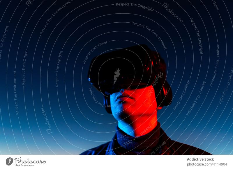 Young man exploring virtual reality night vr dark street headset goggles futuristic illuminate neon red light male modern device gadget 3d sky technology