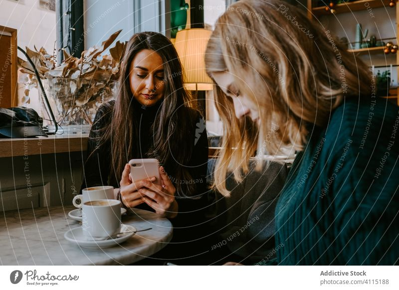 Female friends resting in cozy cafe women together coffee smartphone using joke casual weekend young meeting restaurant drink cup beverage coffee shop cheerful
