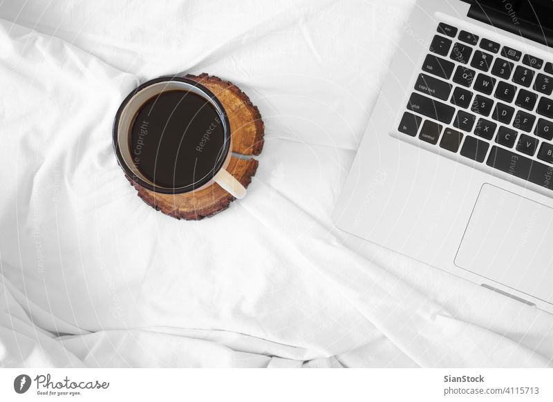 Coffee in bed, top view, coffee white cup shadow laptop morning hotel blanket background home house room apartment lobby light beautiful isolated flower