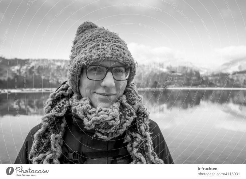 Woman with wool cap and wool scarf in front of a mountain lake portrait Scarf Wool Woolen hat Cap Winter Cold Lake Lakeside Face Adults Clothing Alps
