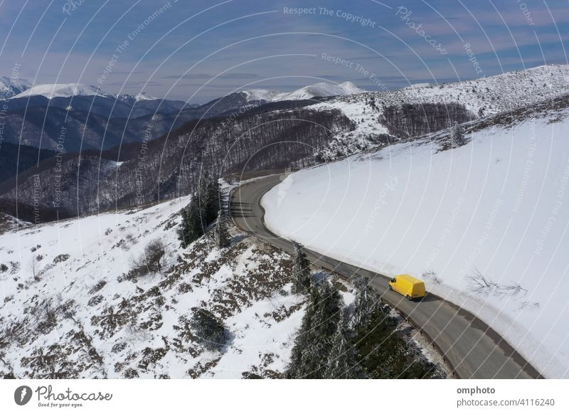 Microbus Truck Moving on a Mountain Winter Road truck car snow winter mountain vehicle yellow snowy road white drive transportation landscape cold weather