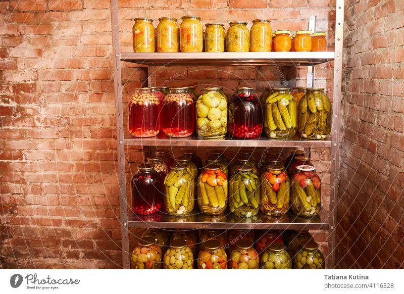 storage of vegetables and fruits for the winter. Shelving with banks with blanks in the home cellar. background canning food glass nature reserve basement