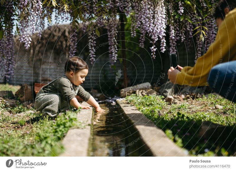 Mother photographing child playing with water Mother with child Child 1 - 3 years Caucasian color Playing Water Curiosity Innocent explore Cute Woman Love