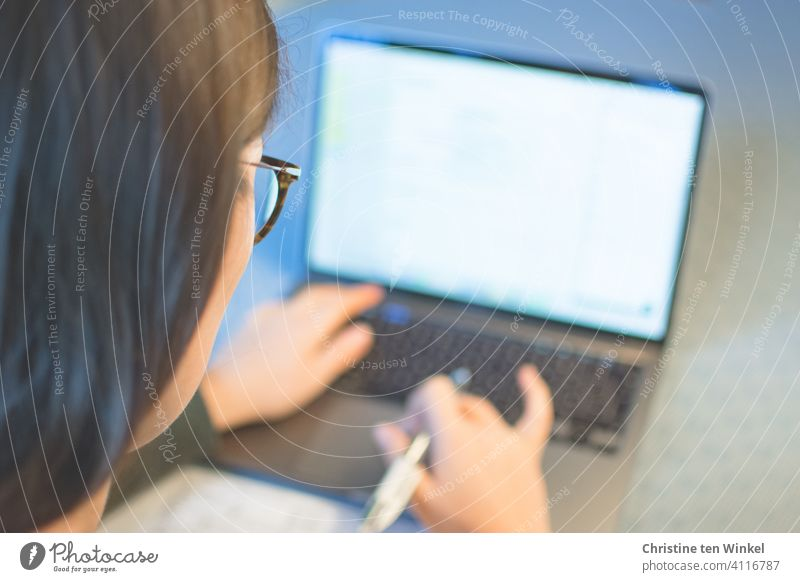 Looking over the shoulder of a young woman with glasses working on a notebook at home. Home office. Online lecture. Homeschooling. home office online lecture