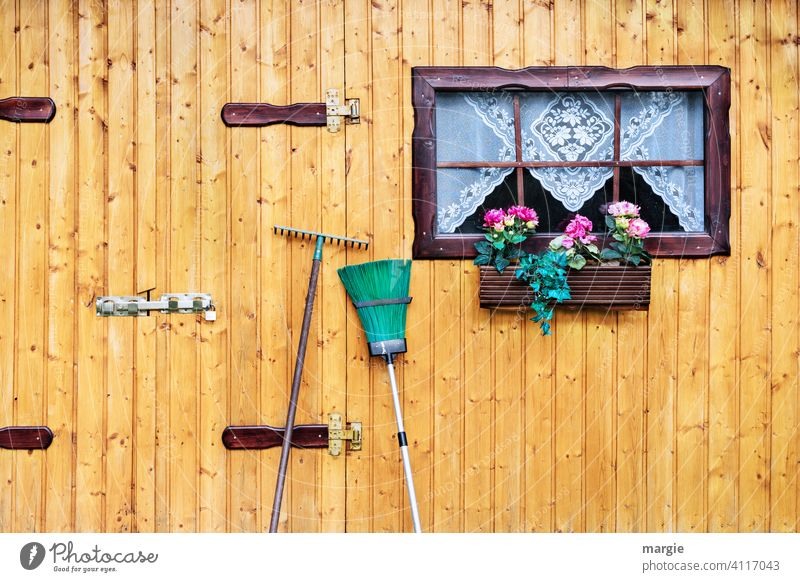 A garden hut with window, curtain, flower box, broom and rake leaning in front of it. Gardening garden shed Window flowers Window box Broom Rake
