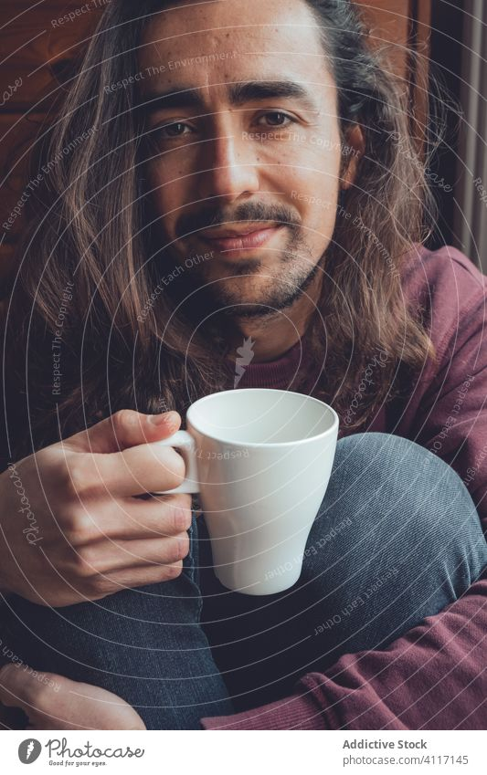 Bearded man resting with hot beverage drink home stay at home coronavirus covid-19 cozy mug mood adult room male relax tea coffee cup comfort long hair beard