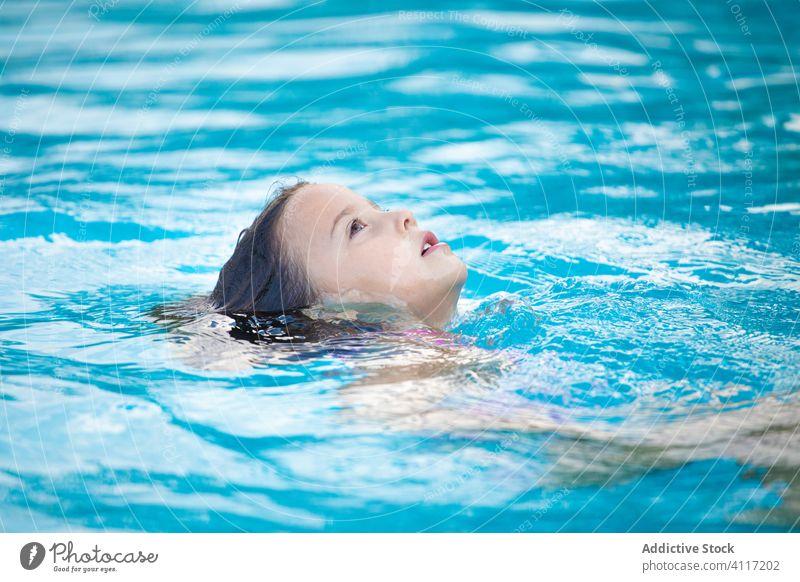 Little girl floating in pool water relax joy clean wet swim kid child rest resort lifestyle summer cute adorable pleasure recreation weekend serene tranquil