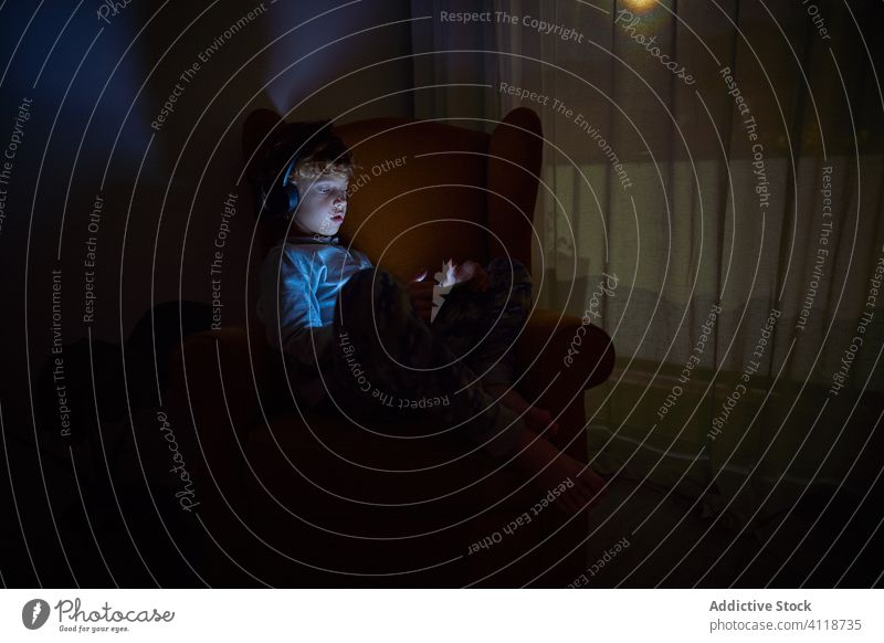 Child sitting in an armchair in a corner of a room watching a tablet with headphones at night boy helmet music listen game play device draw education screen