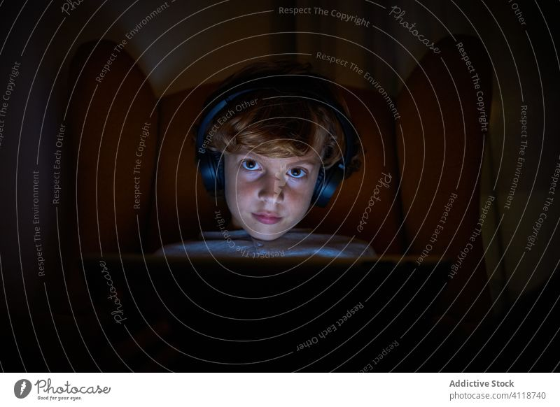Child sitting with headphones on a sofa with tablet computer looking frontally at night boy distracted imagination cinema multimedia communication listen play