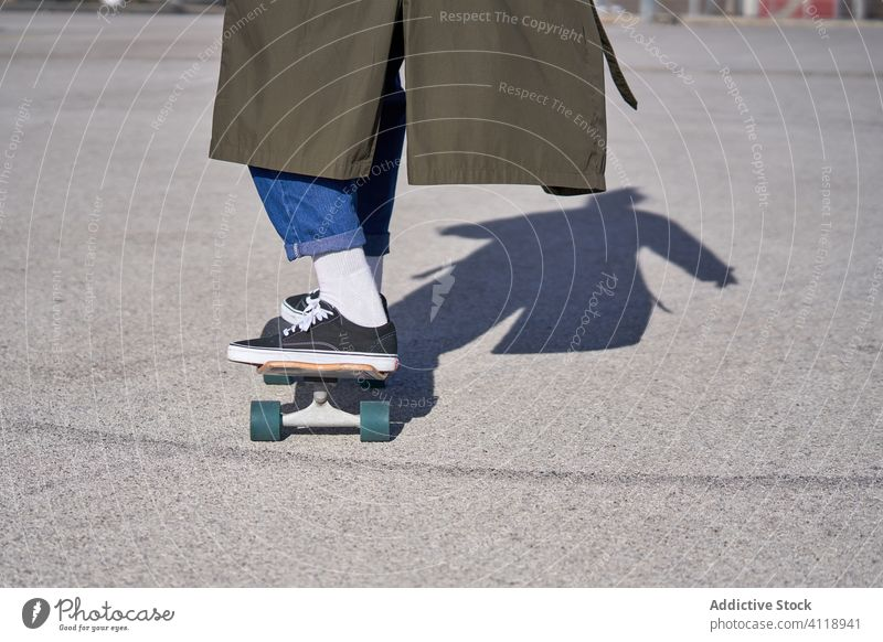 A Man skating on a skateboard on the road with his raincoat and city guy sports people concrete urban asphalt recreation sunny skateboarding street extreme