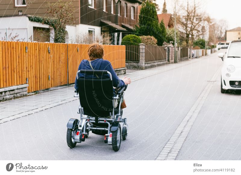 Woman riding an electric wheelchair on the street. People with disabilities and mobility. power wheelchair handicap Street Mobility Wheelchair Human being
