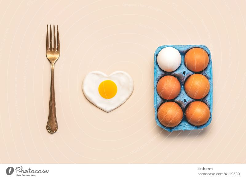 Top view of chicken eggs in an open blue cardboard box with a vintage fork and a heart-shaped fried egg easter eggs fresh egg yolk eat container love basket