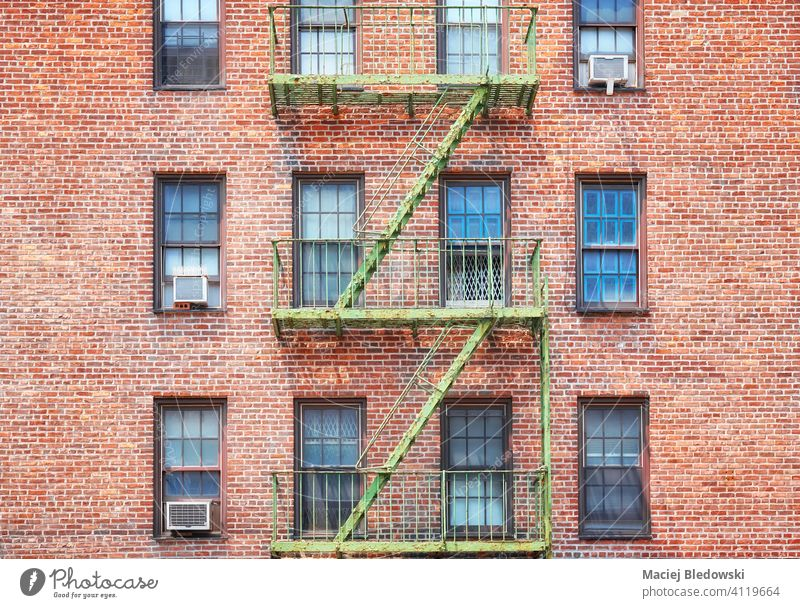 Old brick building with green fire escape, New York City, USA. city Manhattan old townhouse architecture stairs apartment facade NYC ladder residential urban