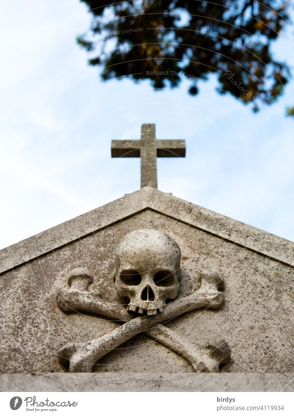 Christian cross with a skull underneath in a cemetery , frog perspective Crucifix Death pass away Cemetery Grave Religion and faith symbolism Climate change