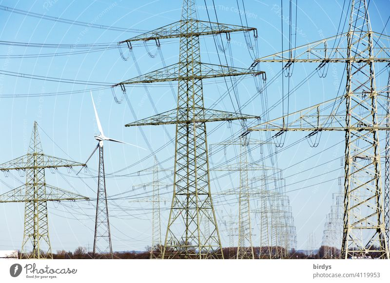 Gigantic power line, high-voltage lines on high pylons. At the edge a wind turbine, format filling Power lines Electricity current highway Power transmission