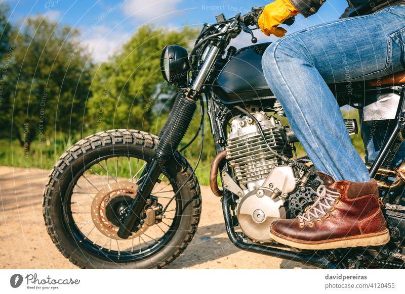 Man riding custom motorbike unrecognizable man motorcycle profile vintage gloves holding grabbing handlebar stopped cool built cafe racer retro rider vehicle