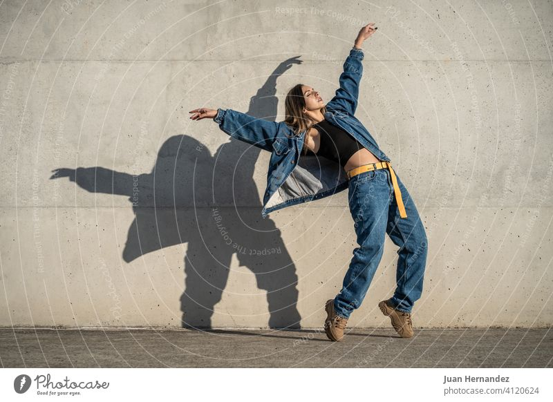 dancer woman making a pose like an eagle. Casual dress and shadow reflected on the wall. casual copy space copy-space copyspace balance exercising performer