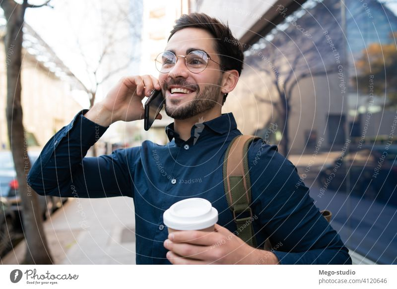 Young man talking on the phone outdoors. young mobile urban coffee take away connection gadget portrait drinking wireless telephone holding walking looking
