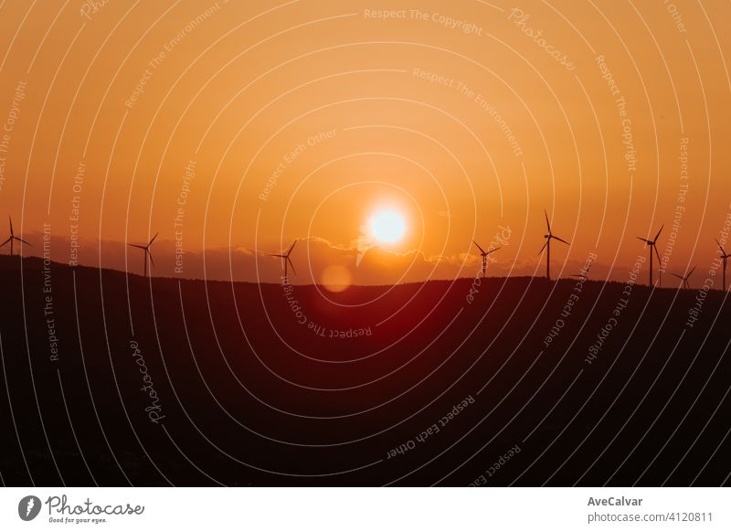 Silhouettes of some wind mills on the top of a mountain during a super orange sunset with copy space peaceful windmill plant energy renewable industrial