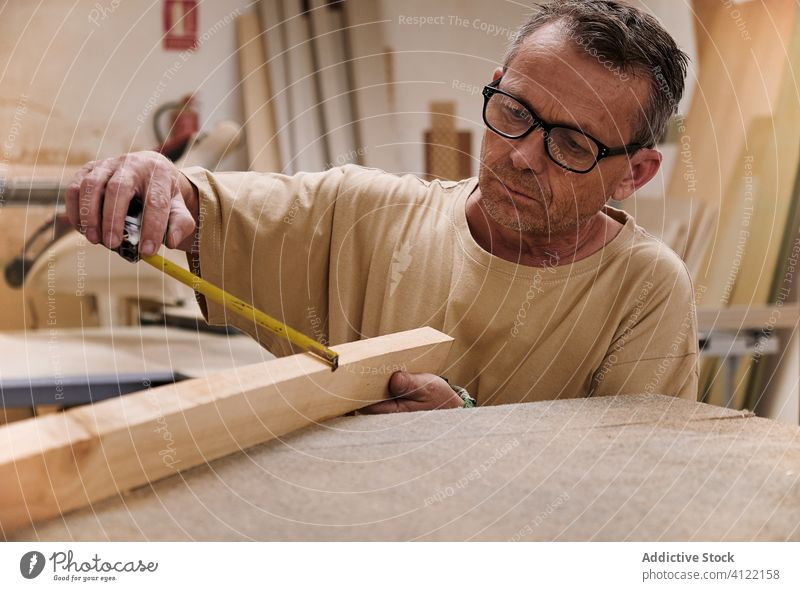 Attentive craftsman using measuring tape while working with lumber in carpentry studio worker control attentive tool precise detail handyman timber wood size