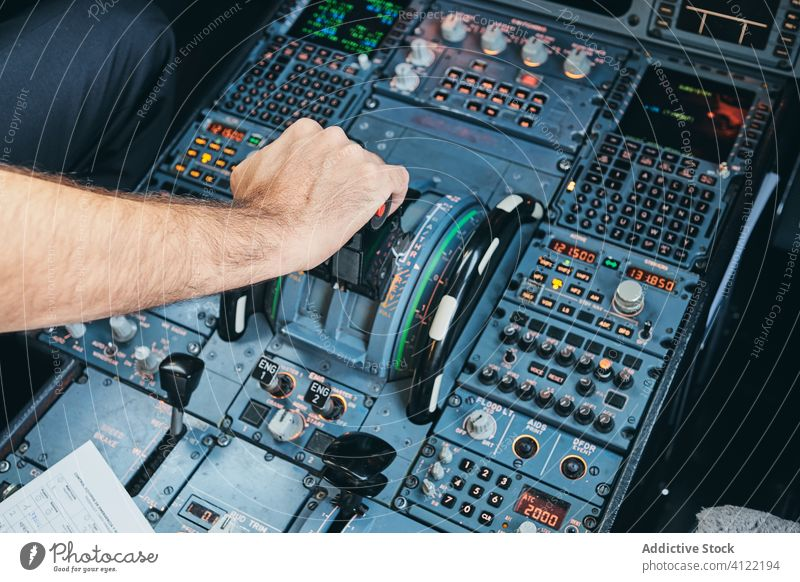Pilot operating airplane in cockpit pilot operate lever man flight control dashboard hand male aviator modern aircraft transport aviation professional push jet