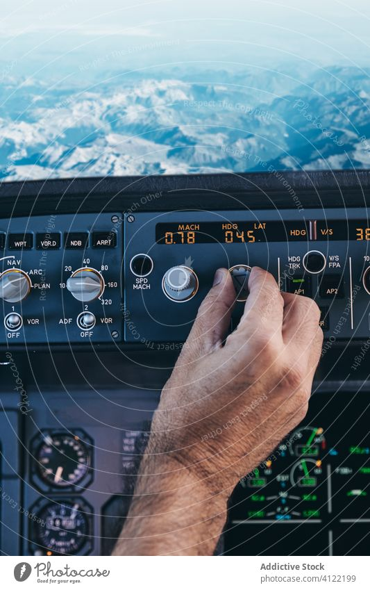 Pilot working with control console during flight pilot cockpit operate man hand switch airplane dashboard rock mountain equipment male aviator check modern
