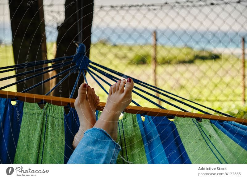 Woman lying in hammock in courtyard woman relax enjoy summer weekend barefoot sunny female tropical vacation calm landscape scenery exotic holiday legs crossed
