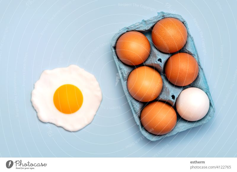Top view of chicken eggs in an open blue cardboard box and a fried egg easter eggs fresh egg yolk eat container basket farming storage farmyard animal egg