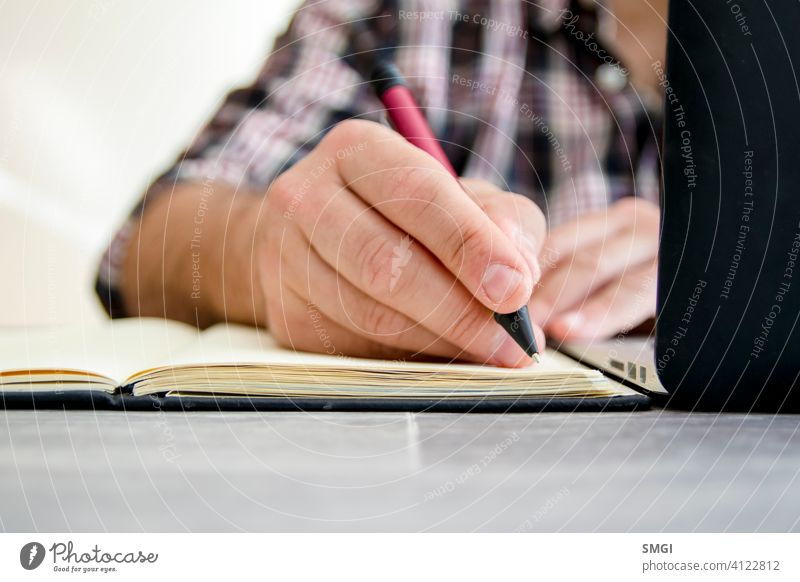 A man writing in a notebook next to a laptop e-learning person education computer online business home technology studying lifestyle internet office homework