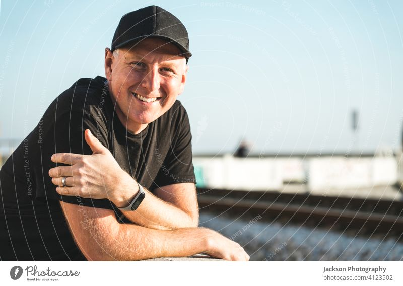 Outdoor portrait of smiling man in his 40s outdoor positive smile sunny cap jockey cap looking at camera copy space joy human healthy mid middle-aged relaxed