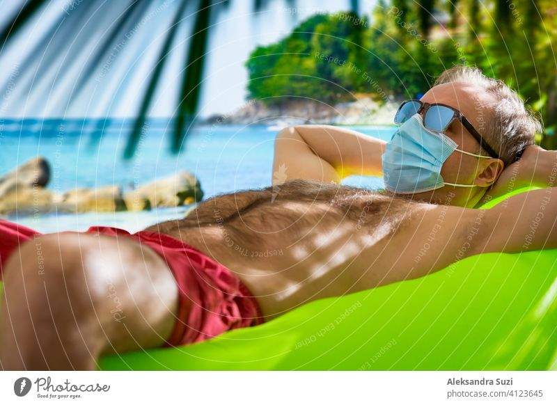 Mature man in protective mask and sunglasses relaxing on beach. Exotic tropic landscape with turquoise water and palms. Tourism during pandemic. Safe traveling.