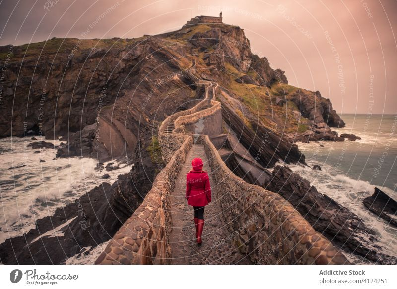 Woman walking on stone bridge surrounded by sea in Basque Country tourist woman seashore spain warm travel explore island trip journey vacation tourism holiday