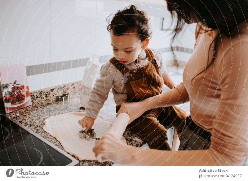 Cheerful little boy cooking pastry with mother in kitchen helper dough bonding cheerful food parent assistant smile together flour prepare child happy home