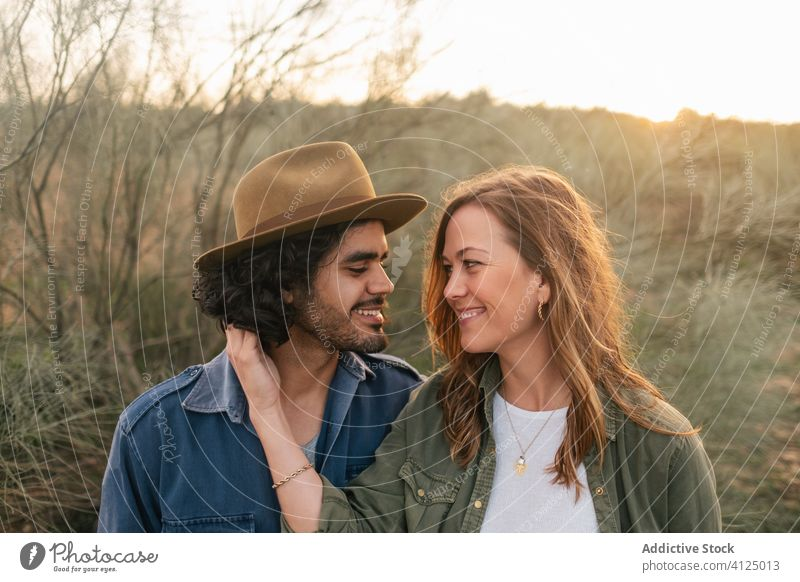 Happy couple hugging in countryside evening date love bush happy tender sunset man woman cheerful romantic lifestyle smile leafless nature relationship together