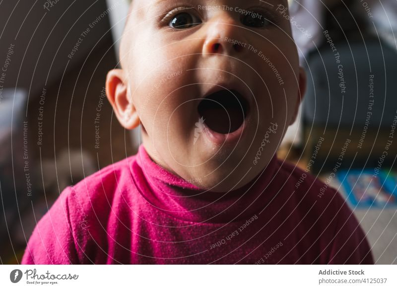 Funny little boy sitting at home and looking at camera amazed wow speechless mouth opened play cheerful cute floor omg charming toddler smile child fun sweet