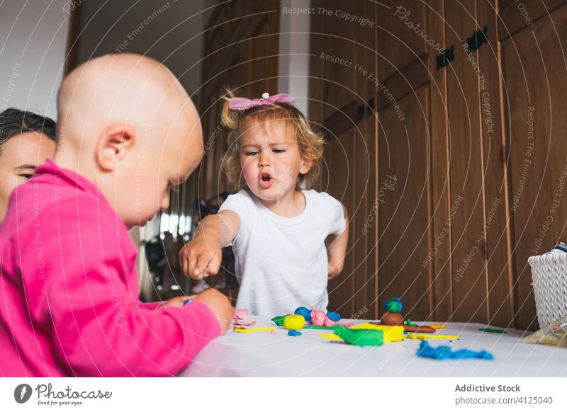 Cheerful siblings playing with modeling clay at home children colorful mother upbringing development preschool excited boy girl charming wow learn fun joy cute