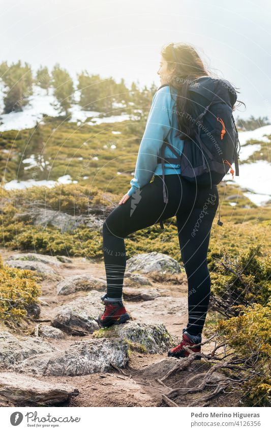 woman hiker standing in the mountain with sunlight. travel snowy landscape nature copy space female top freedom adventure hiking backpack peak rock cliff sky