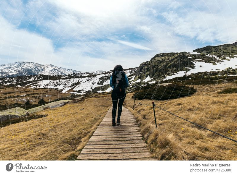 Woman hiker walking along the way to the snowy mountains. winter landscape hiking nature travel tourism adventure woman tourist backpack trail outdoor sky