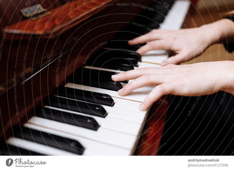 Close up of the hands of a young woman playing piano music key instrument female player keyboard musical close girl caucasian closeup style white human art