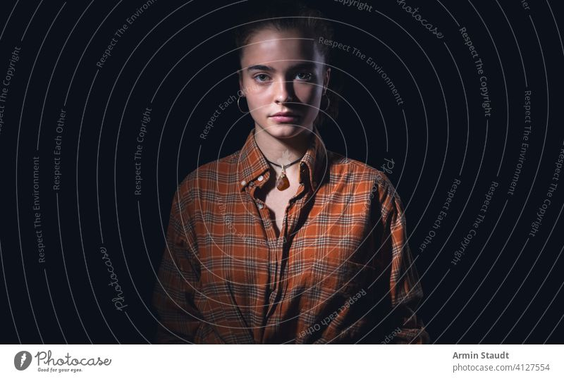 portrait of a beautiful teenage girl with orange plaid shirt woman standing studio serious mysterious human black isolated powerful confident teenager female
