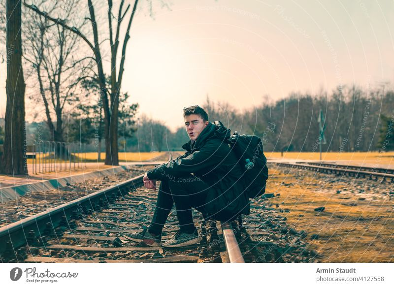 happy young man with backpack sitting on train tracks youthful Man Sit Railroad Tracks Backpack Landscape Outdoors fortunate Smiling Self-confident Powerful far
