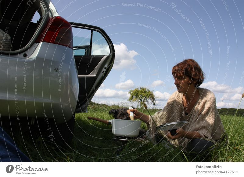 Woman sits in the green next to a car and stirs in a cooking pot boil Trip excursion to the green Freedom trip road trip travel Picnic enjoy nature simple life