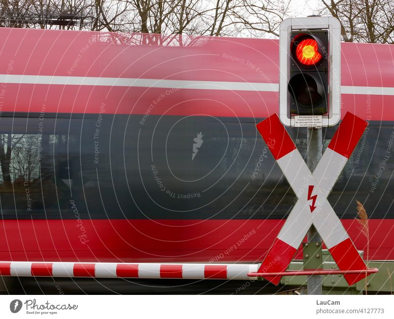 A red train rushes past a closed level crossing with a red-white barrier and red traffic light Railroad crossing Train Train travel Track Control barrier