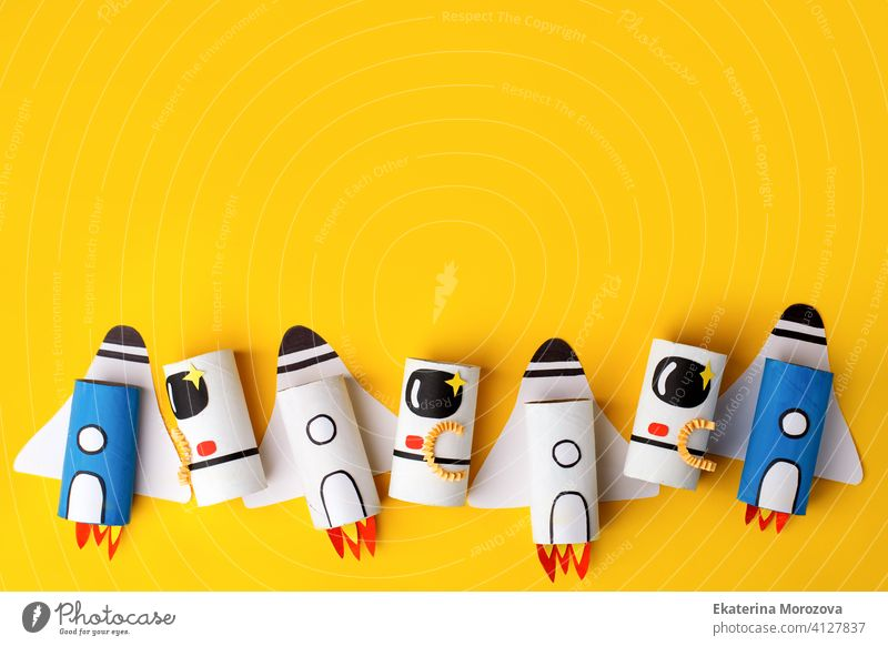 School kindergarten crafts, paper spaceship, shuttle, astronaut on yellow background with copy space for text. Party, start up launch concept, diy, creative idea from toilet tube, recycle
