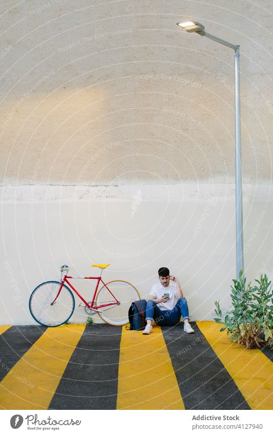 Man sitting on the floor with a bike bicycle fixie urban wheel fixed sport transportation gear lifestyle wall street hipster ride pedal man biking chain action