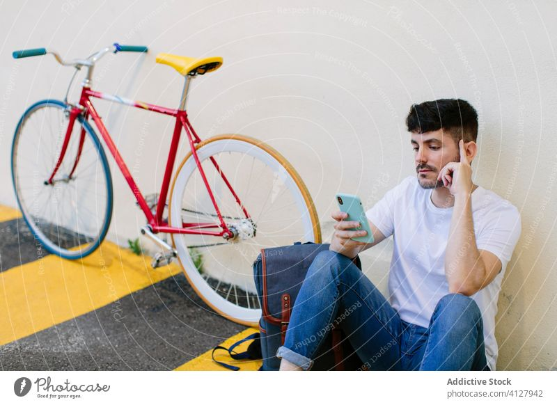 Man checking his smartphone sitting on the street floor bicycle bike fixie urban wheel fixed sport transportation gear lifestyle wall hipster ride pedal man