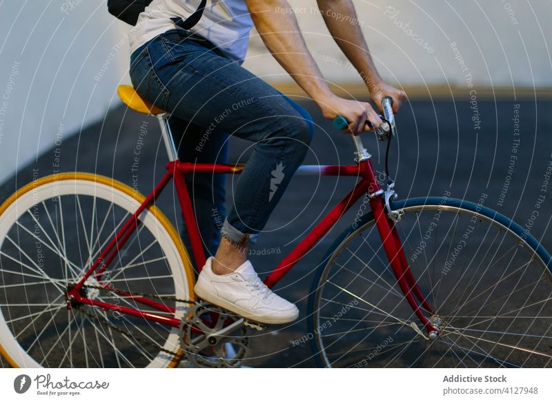 Unrecognizable man riding a bike bicycle fixie urban wheel fixed sport transportation gear lifestyle wall street hipster ride pedal biking chain action cyclist