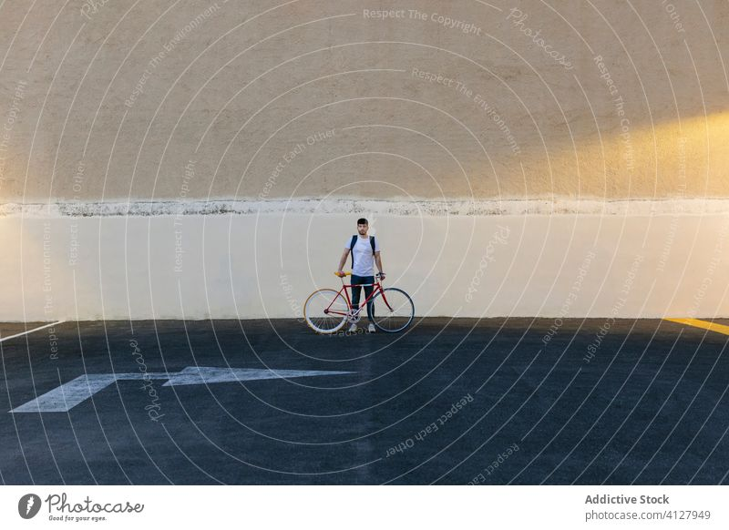 Man with a bike in the middle of a car park bicycle fixie urban wheel fixed sport transportation gear lifestyle wall street hipster ride pedal man biking chain