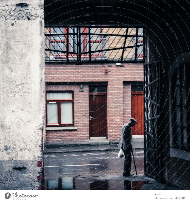 out from the rain Human being Man Old City Loneliness Cold Wall (building) Life Senior citizen Death Sadness Architecture Wall (barrier) Building Time Rain
