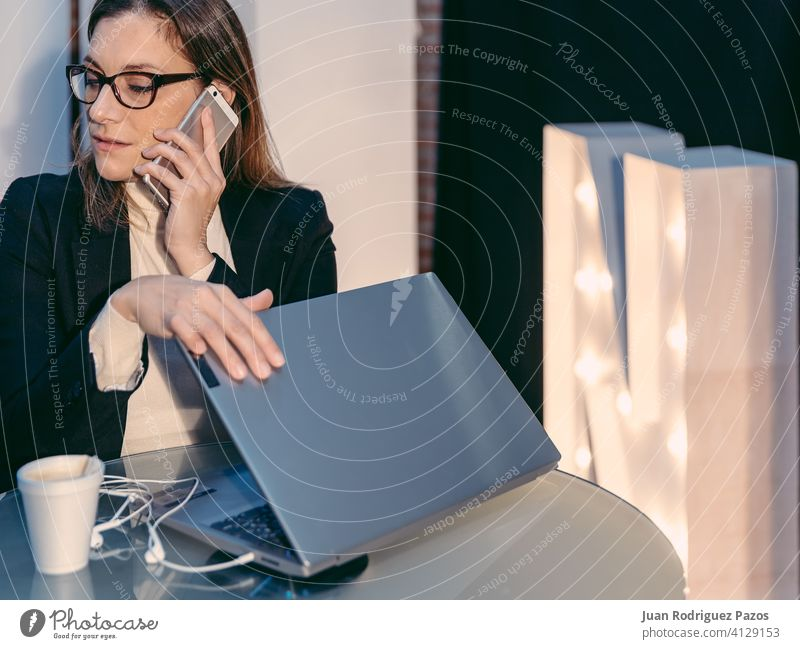 woman having phone conversation while closing laptop computer in cafe bar Laptop business person lady chat call device girl internet blonde digital female